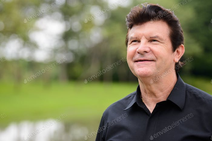 Portrait of mature handsome businessman relaxing at the park