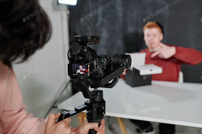 Video operator holding camera in front of vlogger opening black box in studio