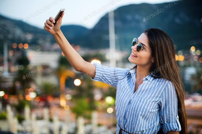 Happy young woman taking selfie on vacation