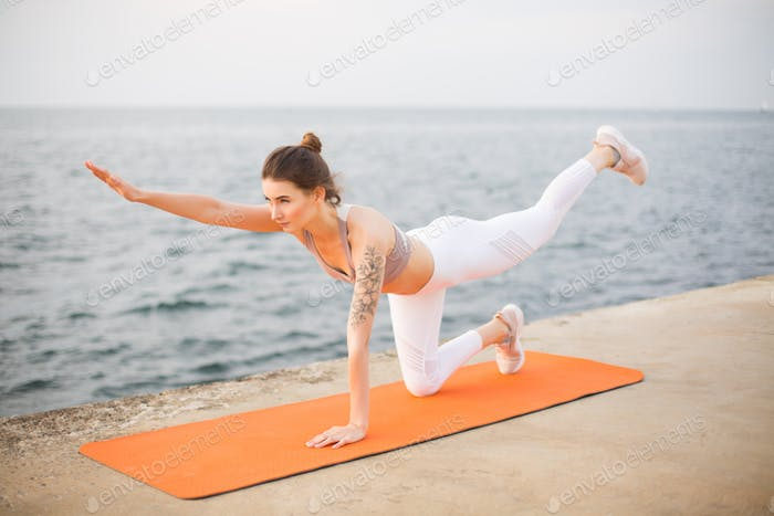 Young woman thoughtfully practicing yoga by the sea. Pensive gir