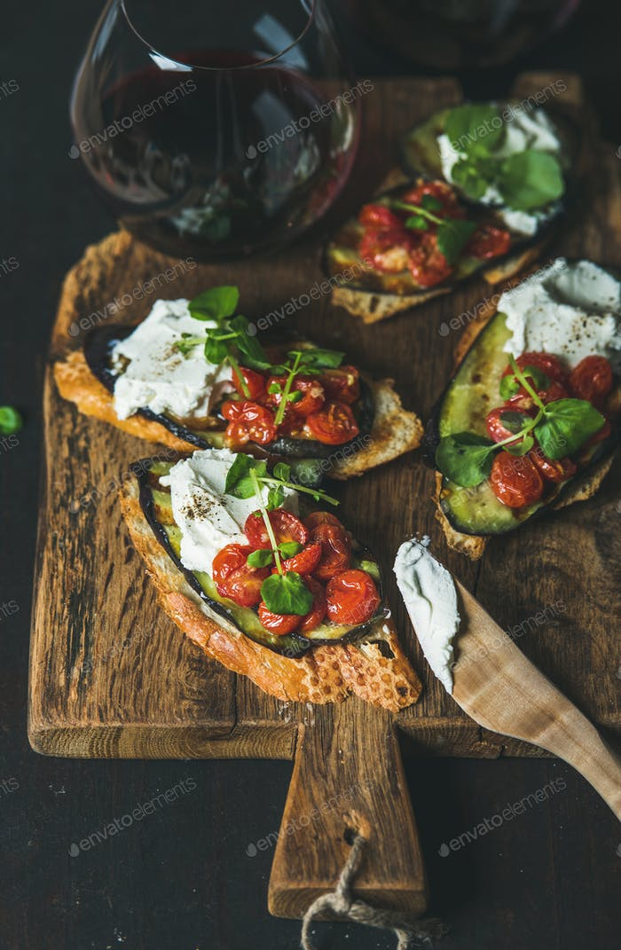 Bruschetta with grilled vegetables, cream cheese, arugula and red wine