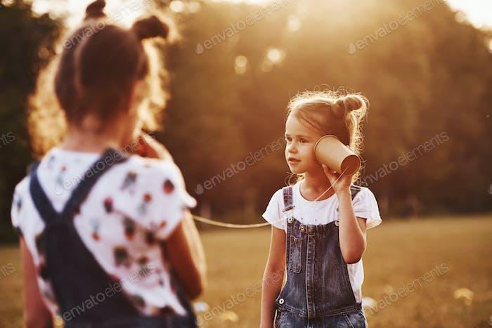 Zwei weibliche Kinder steht auf dem Feld und sprechen mit String können Telefon
