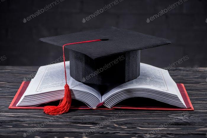Libro abierto con tapa de graduación sobre mesa de madera