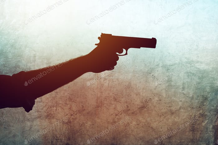 Hand with a gun on grunge background