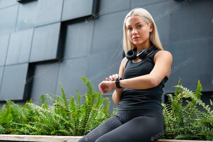 Женский бегун проверяет производительность тренировки на смарт-часе