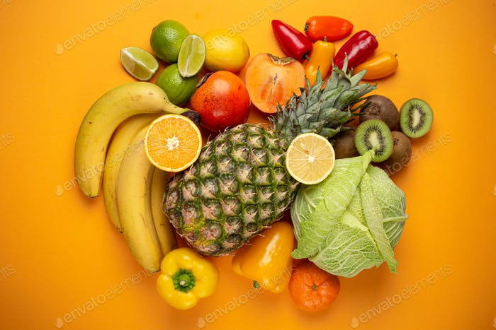 Fruit, citrus, vegetables with vitamin C, yellow orange background top view