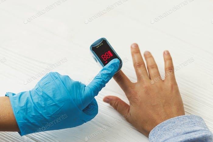 Doctor measuring blood oxygen level with portable Pulse Oximeter on hand, detecting coronavirus
