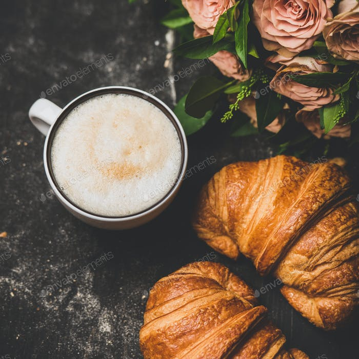 Cup of cappuccino, fresh croissants and pink flowers, square crop