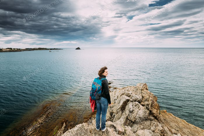 Young Woman Backpacker Hiker Enjoying Sea View On Top Of A Coast