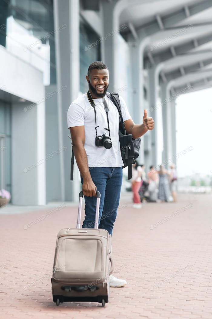 Happy african american guy with suitcase showing thumb up at airport