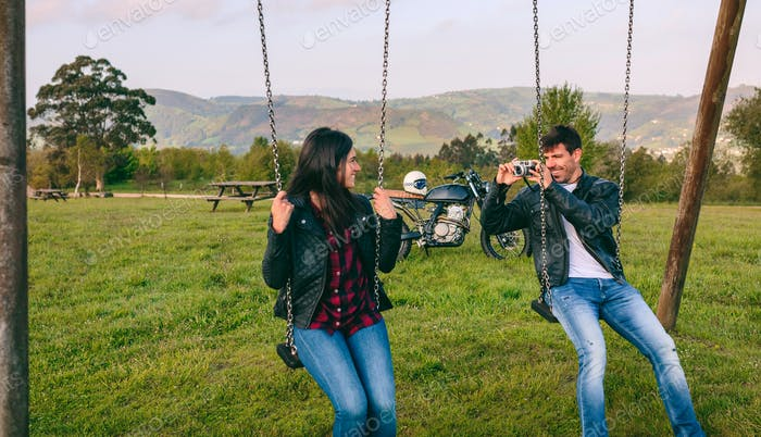 Young man taking a picture of his girlfriend on the swings