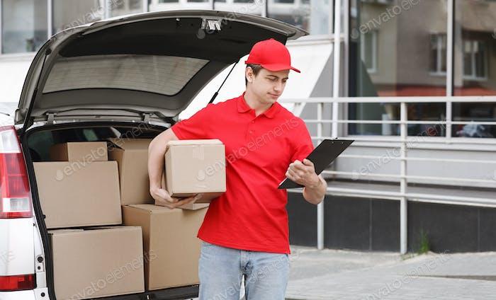 Moderne Post und Lieferung mit dem Auto. Kurier schaut auf das Tablet und hält die Box