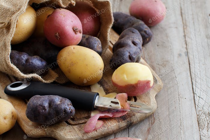 Raw potatoes with a vegetable peeler