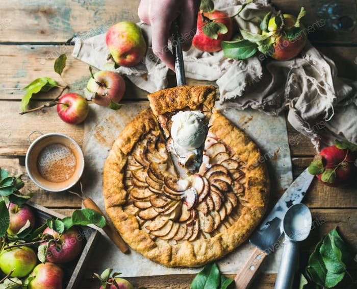 Man's hand holding piece of apple crostata pie