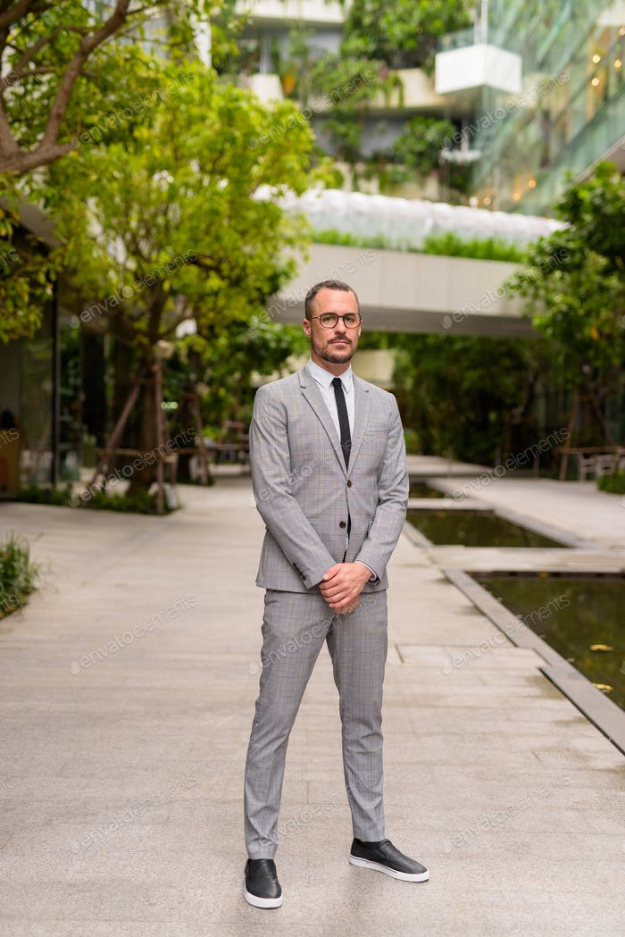 Full body shot of Hispanic bald bearded businessman wearing eyeglasses with nature in the city