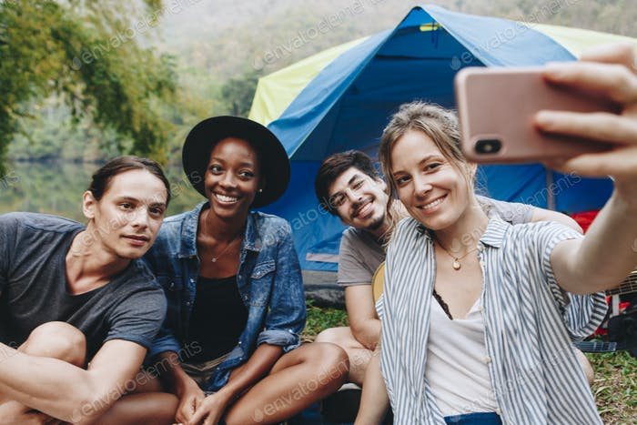 Group of friends taking a selfie at a campsite