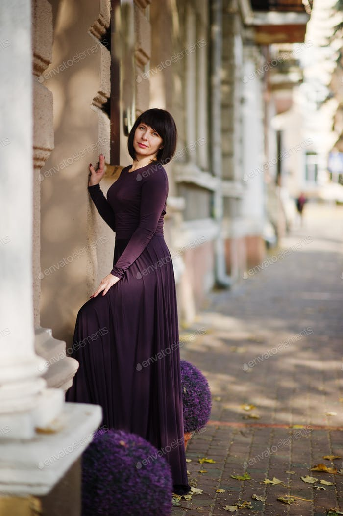 Adult brunette woman at violet gown on autumn fall background.