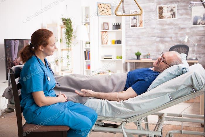 Senior man in nursing home talking with female nurse