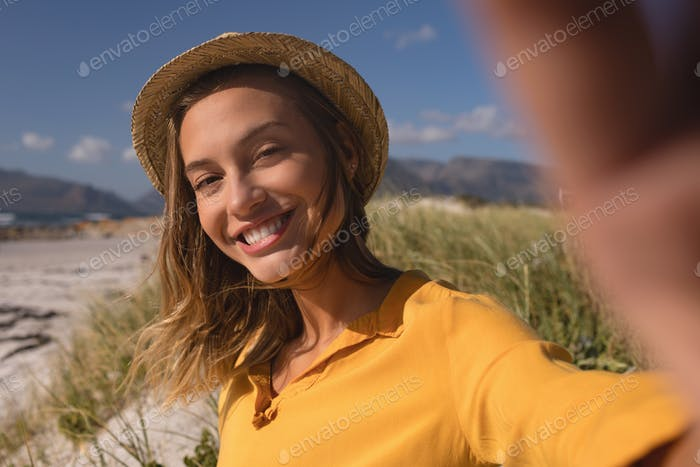 Portrait of woman wearing hat relaxing on the beach on a sunny day