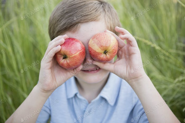 A boy holding two red skinned apples over his eyes.