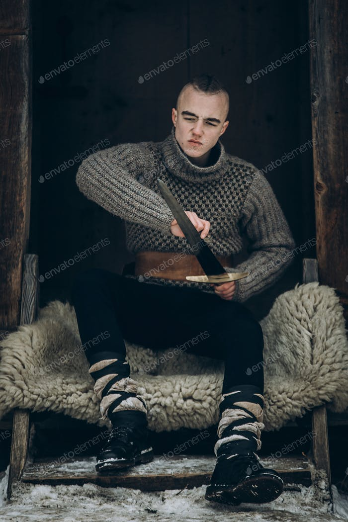 Portrait of strong viking warrior sharpening his sword, scandinavian viking cosplay