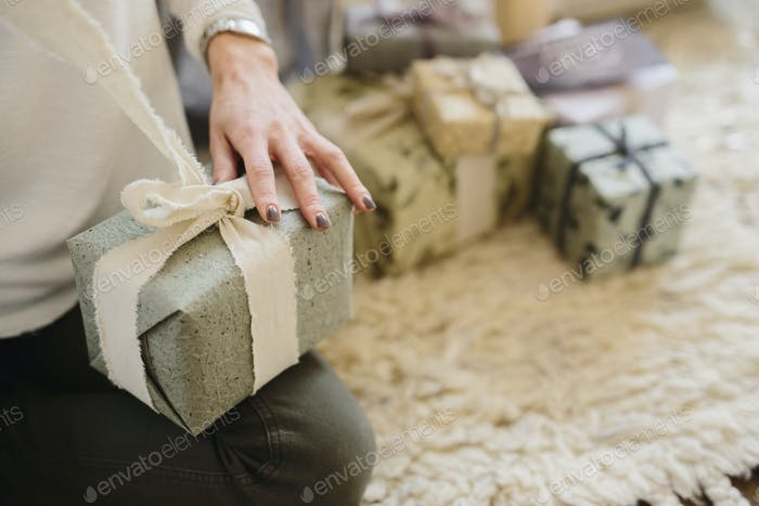 A woman sitting with a pile of wrapped presents.