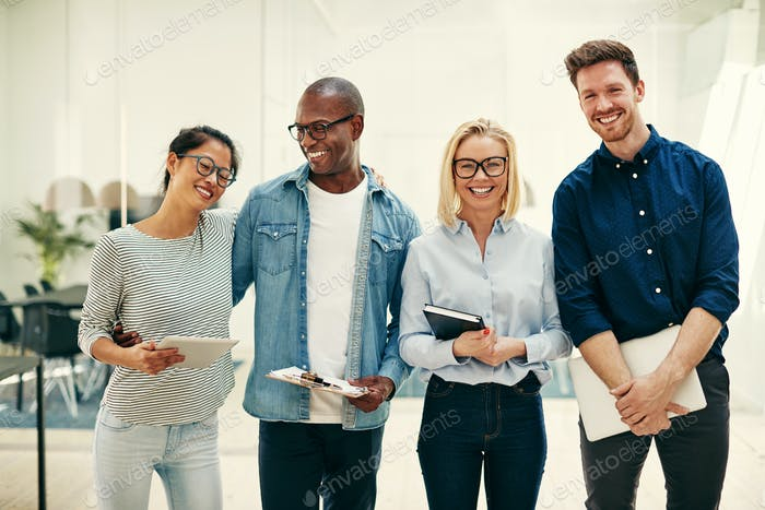 Laughing group of young businesspeople working together in an office