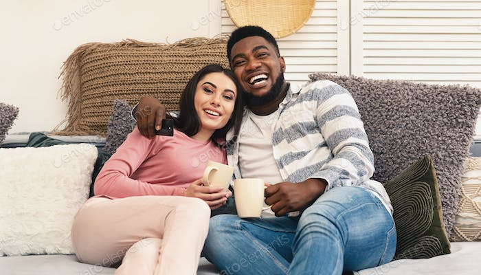 Glad multiracial millennial family resting at home