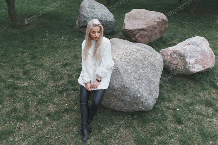 Blonde Hair beautiful female wearing in knitted white sweater and black leather pants