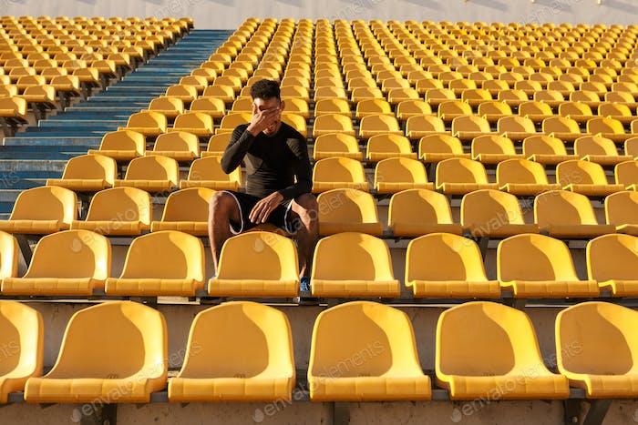 African American Sportler bedecken Gesicht mit Hand ruht nach Lauf unter leeren Stadionsitzen
