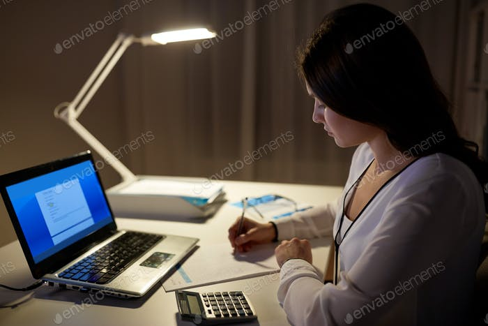 woman with calculator and papers at night office