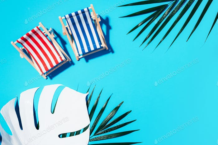 Two deck chairs with hard shadow, monstera and palm leaves on blue paper background. Flat lay and