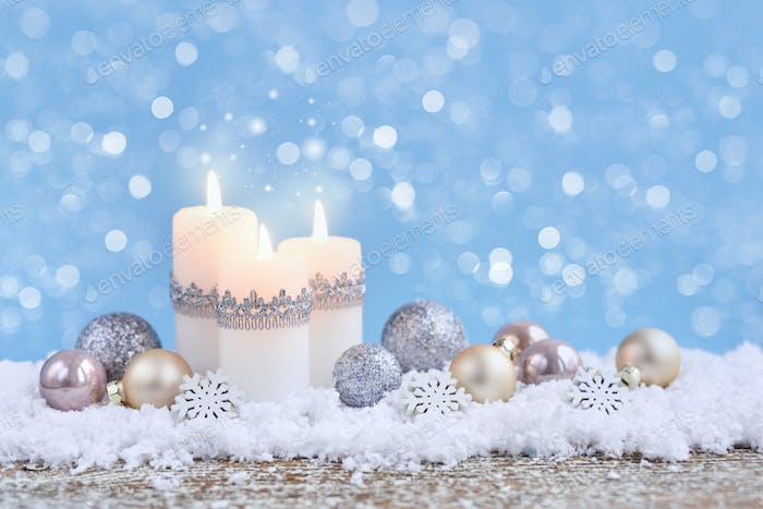 Christmas composition with candles and festive decorative balls on the snow. New Year greeting card.
