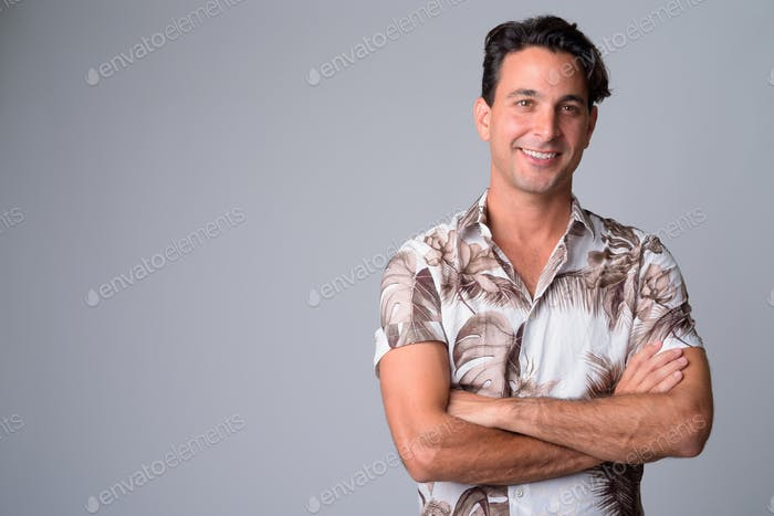 Portrait of happy handsome Hispanic tourist man thinking with arms crossed