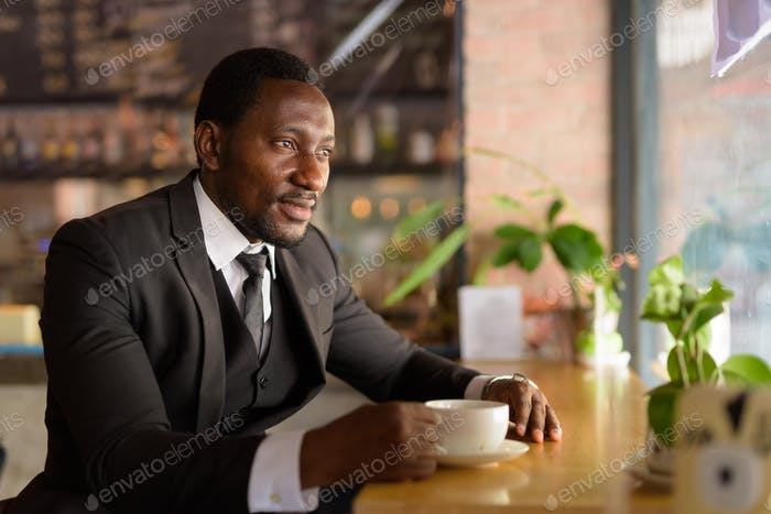 Happy handsome bearded African businessman thinking at the coffee shop
