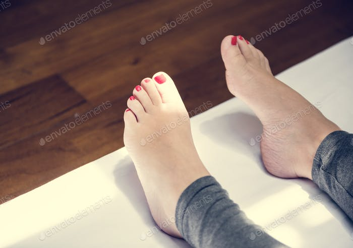 Closeup of a pair of feet with red nail polish