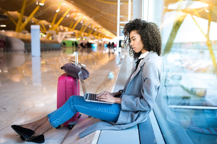 black woman working with laptop at the airport waiting at the wi