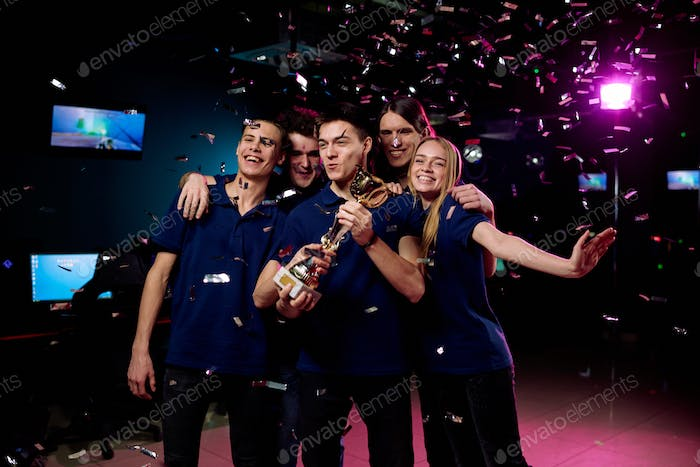 Group of five teenagers celebrating their victory in cybersports competition