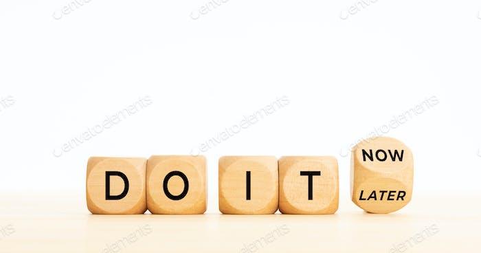 Do it now vs do it later phrase on wooden blocks