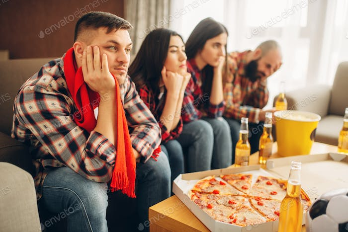 Sad friends watching TV at the boring house party