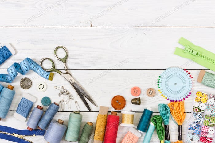 Tools and accessories for sewing on light wooden background.