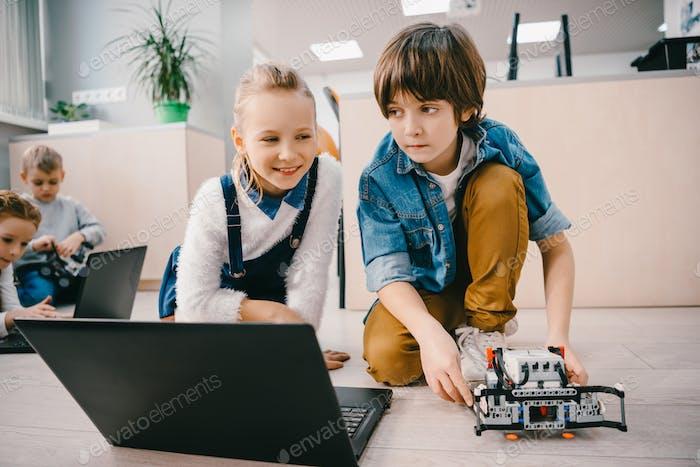 kids programming robot on floor at machinery class