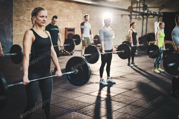 Group of adults holding heavy barbells