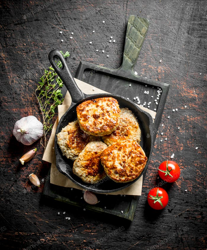 Cutlets in pan on paper with thyme,garlic and tomatoes.