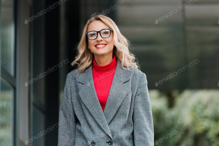 attractive businesswoman in coat and glasses smiling and looking away