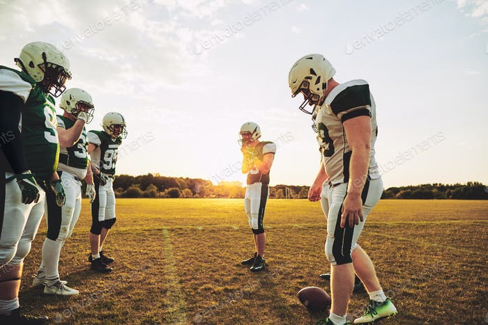 Football players lining up for practice on a sports field
