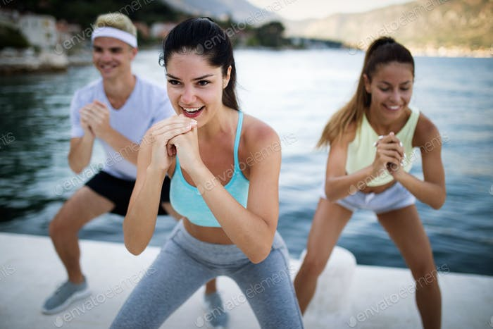 Fit group of happy people exercising outdoor. Smiling friends doing fitness workout