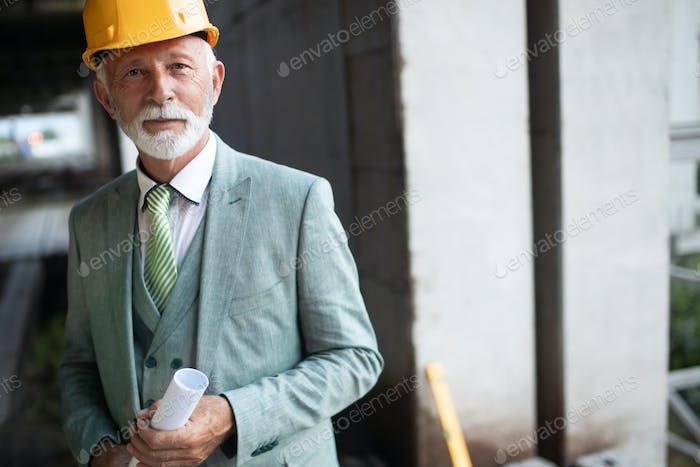 Portrait of an handsome senior engineer, architect, businessman on construction site
