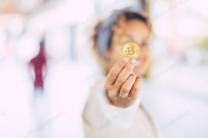 Mujer caucásica moderna alegre en el mundo de los negocios que muestra una criptomoneda bitcoin de oro
