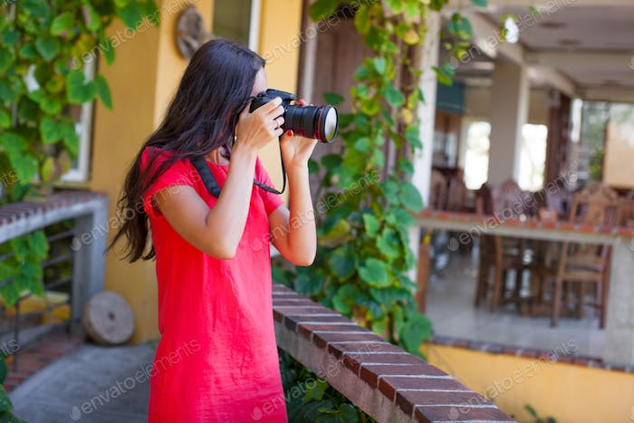 Young brunette woman with camera in the courtyard of beautiful house
